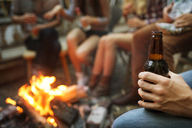 Cropped image of man holding beer bottle while camping with friends - CAVF07087