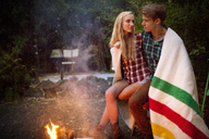 Romantic couple wrapped in blanket sitting by bonfire - CAVF07090