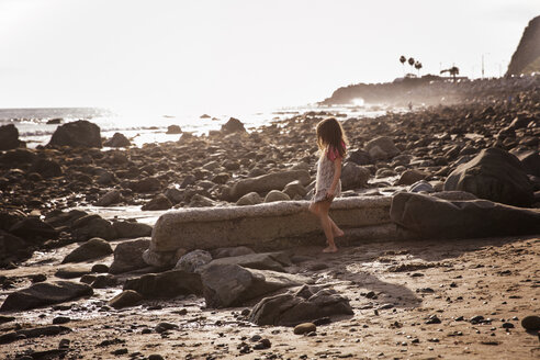 Side view of girl standing at rocky beach during sunset - CAVF07114