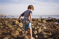 Rear view of boy with binoculars walking on rocks at beach - CAVF07120