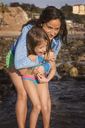 Happy mother embracing girl at beach - CAVF07126