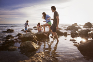 Couple holding hands while walking with playful children at beach - CAVF07132