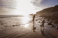 Father and son throwing stones in sea during sunset - CAVF07138