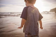 Midsection of boy at beach during sunset - CAVF07141