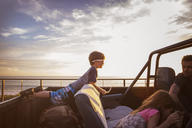 Family in pick-up truck by sea during sunset - CAVF07153