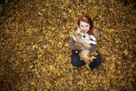 High angle view of woman embracing dog while sitting on autumn leaves - CAVF07198