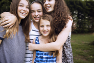Portrait of friends embracing while standing on field - CAVF07252