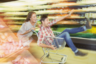 Blurred view of couple playing with shopping cart in grocery store - CAIF15559