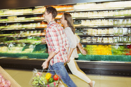 Blurred view of couple shopping together in grocery store - CAIF15586
