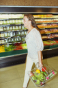 Blurred view of woman carrying full shopping basket in grocery store - CAIF15592