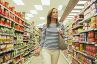 Woman shopping in grocery store aisle - CAIF15595