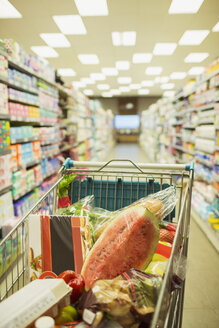 Full shopping cart in grocery store aisle - CAIF15601