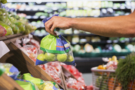 Man holding bag of produce in grocery store - CAIF15604