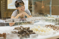 Clerk smiling behind candy counter in store - CAIF15607