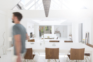 Blurred view of man walking in modern dining room - CAIF15658