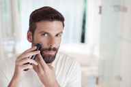 Man trimming beard in bathroom mirror - CAIF15667