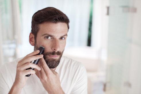Man trimming beard in bathroom mirror - CAIF15667