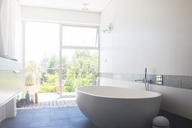 Modern bathroom with large white bathtub and patio door - CAIF15682