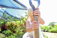 Girl holding shovel in sunny garden - CAIF15712