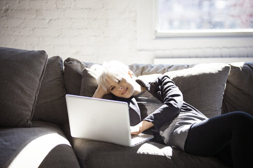 Happy woman using laptop on sofa at home - CAVF07424