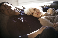 Thoughtful multi-ethnic couple relaxing on sofa at home - CAVF07430