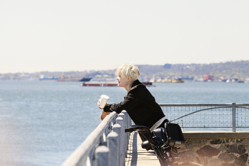 Woman leaning on railing at observation point by river against clear sky - CAVF07508