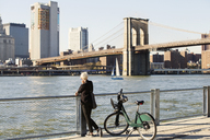 Woman looking at Brooklyn Bridge over East River while standing on promenade - CAVF07523