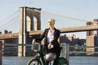 Woman standing with bicycle and helmet against Brooklyn Bridge in city - CAVF07526