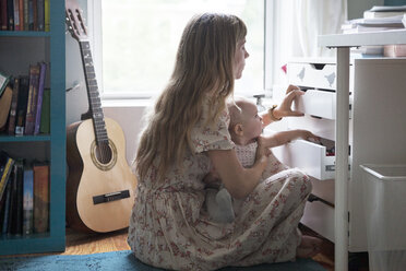 Mother and baby opening drawers at home - CAVF07541