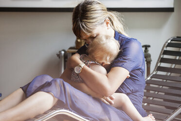 Mother embracing daughter while sitting on lounge chair at home - CAVF07559