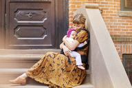 Mother embracing baby while sitting on staircase - CAVF07565