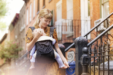 Mother holding baby in carrier while walking against houses - CAVF07568