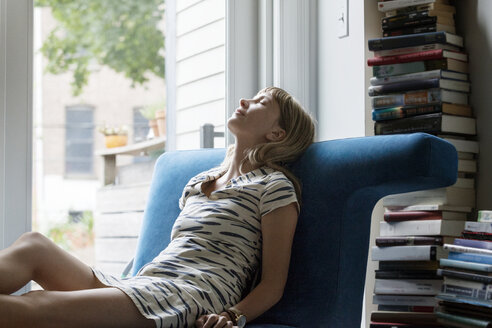 Tired woman relaxing on sofa by window at home - CAVF07574