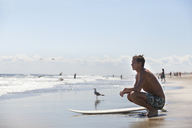 Thoughtful man with surfboard crouching at beach - CAVF07616