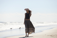 Woman in sun hat walking at shore on sunny day - CAVF07622
