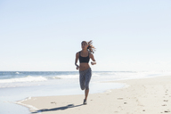 Confident woman jogging on shore at beach against sky - CAVF07625