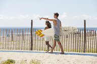 Man pointing while walking with girlfriend by fence at beach - CAVF07628