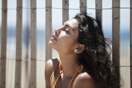 Relaxed woman sitting against fence at beach - CAVF07634
