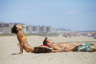 Side view of couple relaxing at beach against blue sky - CAVF07640