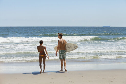 Rear view of couple carrying surfboard at beach - CAVF07643