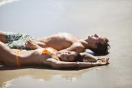 Couple lying at beach on sunny day - CAVF07646