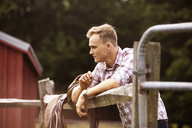 Side view of rancher with saddle in farm - CAVF07655