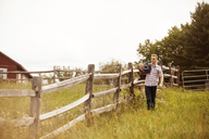 Rancher carrying saddle while walking by fence on grassy field - CAVF07658