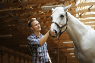 Happy rancher stroking horse in stable - CAVF07667