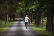 Man walking on road with bicycle in forest - CAVF07673