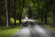 Happy man riding bicycle on road in forest - CAVF07676