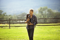 Man carrying dog while walking on grassy field in farm - CAVF07682