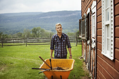 Rancher looking up while pushing wheelbarrow in farm against mountain - CAVF07685