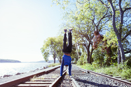 Man doing handstand on railroad tracks by river against clear sky - CAVF07739