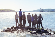 Rear view of friends standing on rocks in river against clear sky - CAVF07742